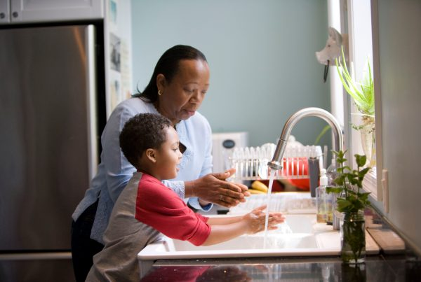 African-American woman washing hands with grandson