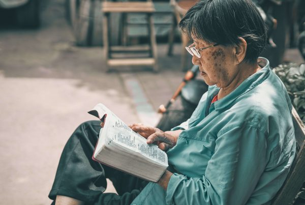 Elderly woman reads a book outside