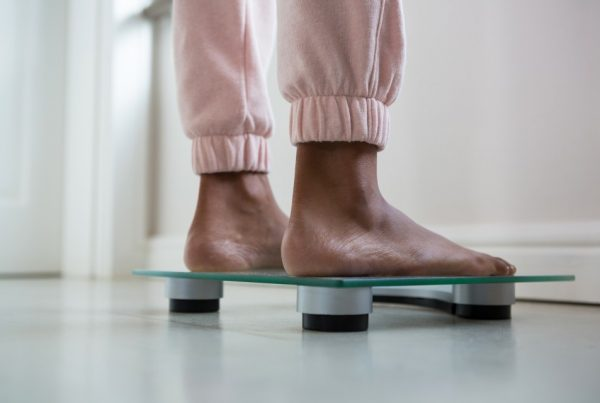 Woman stands on bathroom scale