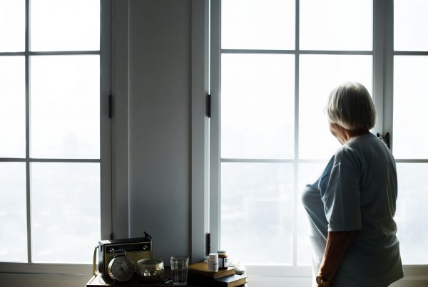 Older adult woman stands alone at home looking out the window